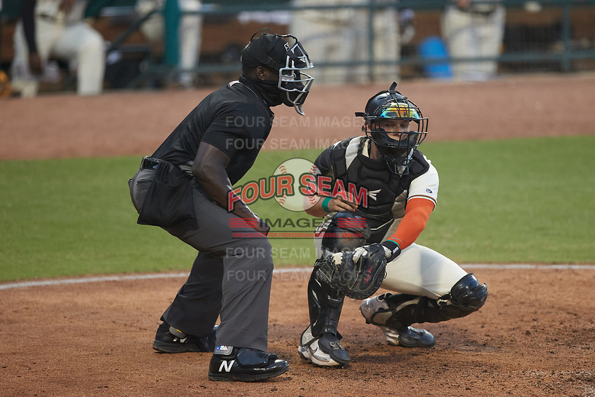 Greensboro Grasshoppers catcher Grant Koch (23) reaches for a pitch as home plate umpire James Jean looks on during the game against the Wilmington Blue Rocks at First National Bank Field on May 25, 2021 in Greensboro, North Carolina. (Brian Westerholt/Four Seam Images)