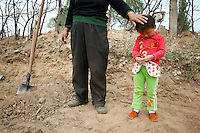 A farmer takes a break with her child whilst working their fields in Hebei Province, China. Desertification is the process by which fertile land becomes desert, typically as a result of drought, deforestation, or inappropriate agriculture. 41 % of China's landmass in classified as arid or desert. Inappropriate farming methods and over cultivation have contributed to the spreading of deserts in China in recent years.
