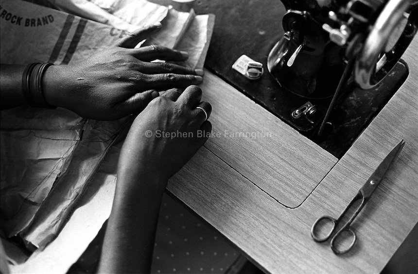 Widows and the Workforce - A workshop that teaches tailoring to widows whose families have been affected by HIV/AIDS is offered at the non-profit organization AOET based in Jinja. The classes teach these women the basics of tailoring and how to further progress in the local economic market. Bugembe, Jinja District, Uganda, Africa. June 2004 © Stephen Blake Farrington