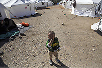 Pictured: A young boy stands by a row of tents Friday 26 February 2016<br />Re: Hundreds of refugees have been given temporary shelter at the Stefanakis Army Camp in the Schisto area of Athens, Greece.