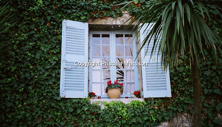 Blue shutters frame the window of a house in France.