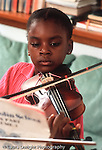 7 year old girl practicing violin at home vertical