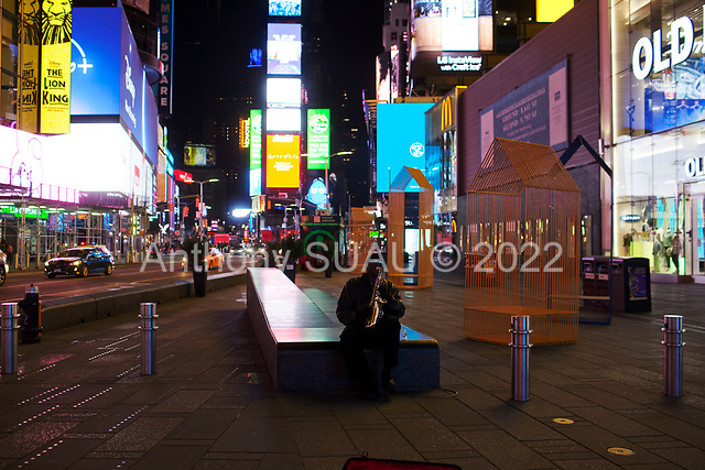 """New York, New York<br /> April 4, 2020<br /> <br /> On a Saturday evening a musician plays a saxophone plays over the empty and haunted Times Square with all Broadway theaters shut down.<br /> <br /> The coronavirus has transformed urban architectural spaces with fear of proximity. Not entirely void of humanity, social distancing, within expansive city environments has created a landscape of aggrandizing physical structures and expanding spaces while diminishing the scale of humans. Face masks enhance the anonymity of """"the person"""", reducing them to a figure or an uninterrupted shadow falling on a surface."""