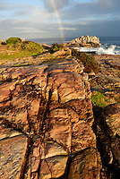 Rainbow on Ocean by a rocky shore, sunset, Hermanus, South Western Cape, South Africa