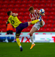 21st November 2020; Bet365 Stadium, Stoke, Staffordshire, England; English Football League Championship Football, Stoke City versus Huddersfield Town; Jonathan Hogg of Huddersfield Town and Sam Clucas of Stoke City jump for the ball and clash boots