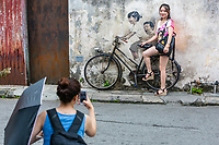 George Town, Penang, Malaysia.  Young Woman Posing for Photo by Street Art by Ernest Zacharevic.