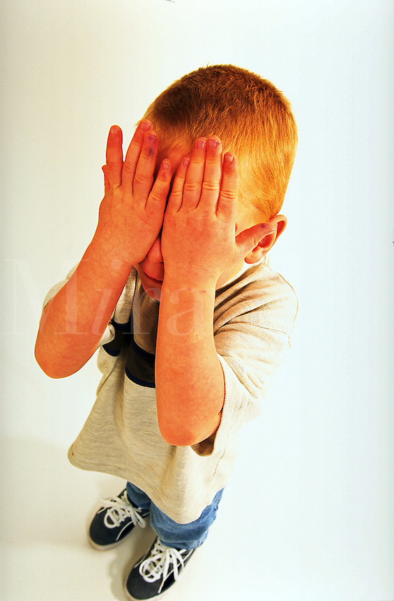 Young boy covering his eyes.