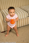 Infant development 9 month old baby girl standing without support holding ball toy