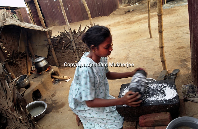 A young woman prepares food for her family in her temporary shelter.Nagapattinam.India.