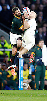 Photo: Richard Lane/Richard Lane Photography. England v South Africa. QBE Autumn International. 15/11/2014. England's Mike Brown is tackle in the air by South Africa's Willie Le Rous.