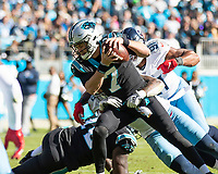 CHARLOTTE, NC - NOVEMBER 3: Kyle Allen #7 of the Carolina Panthers is tackled by Harold Landry #58 of the Tennessee Titans during a game between Tennessee Titans and Carolina Panthers at Bank of America Stadium on November 3, 2019 in Charlotte, North Carolina.