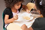 Education preschool 4 year olds meal time breakfast girl helping friend by pouring milk onto her cereal