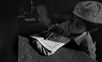 Delhi /  India.A muslim boy reads the Koran in the madrasa near Jama Masjid, the principal mosque of Old Delhi in India..Photo Livio Senigalliesi.