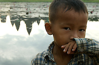 CAMBODIA 2007,SIAM REAP, Young boy and the reflection of Angkor Wat Temple,