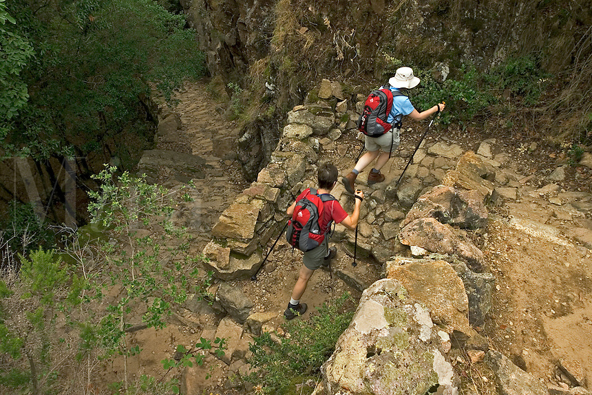 Corsica. France. Walkers in the Gorges de Spelunca on the ancient paved mule track between Evisa and Ota. Corse..