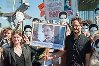 """Snowden-Aktion vor dem NSA-Untersuchungsausschuss.<br />Mitglieder der Piratenpartei hiessen am Donnerstag den 22. Mai 2014 den Whistleblower Edward Snowden vor Beginn der Sitzung des NSA-Untersuchungsausschuss symbolisch willkommen. Mit der Aktion unter dem Motto """"Snowden nach Berlin - fuer einen sicheren Aufenthalt von Edward Snowden in  Deutschland"""" warb die Piratenpartei dafuer, dass Edward Snowden zum Untersuchungsausschuss nach Berlin eingeladen wird. """"Um die Aufarbeitung des Ueberwachungsskandals nicht vollstaendig zur Farce werden zu lassen, halten wir es fuer unabdingbar, Edward Snowden als Zeugen nach Berlin zu laden"""", so die Piraten.<br />Im Bild: Die Piraten Anke Domscheid-Berg und ihr Mann Daniel Domscheid-Berg halten ein Plakat mit einem Bild von Edward Snowden.<br />22.5.2014, Berlin<br />Copyright: Christian-Ditsch.de<br />[Inhaltsveraendernde Manipulation des Fotos nur nach ausdruecklicher Genehmigung des Fotografen. Vereinbarungen ueber Abtretung von Persoenlichkeitsrechten/Model Release der abgebildeten Person/Personen liegen nicht vor. NO MODEL RELEASE! Don't publish without copyright Christian-Ditsch.de, Veroeffentlichung nur mit Fotografennennung, sowie gegen Honorar, MwSt. und Beleg. Konto: I N G - D i B a, IBAN DE58500105175400192269, BIC INGDDEFFXXX, Kontakt: post@christian-ditsch.de]"""
