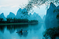 Moody landscape image of Li River Cormorant fisherman on bamboo rafts in the Karst Hills. Guilin Guangxi, China.