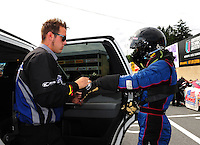 Sept. 30, 2011; Mohnton, PA, USA: NHRA funny car driver Leah Pruett (right) is helped with safety gear by a crew member during qualifying for the Auto Plus Nationals at Maple Grove Raceway. Mandatory Credit: Mark J. Rebilas-