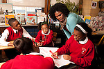 5th grade at parochial school female teacher with students working together on humanties (history social studies) small group discussions and project