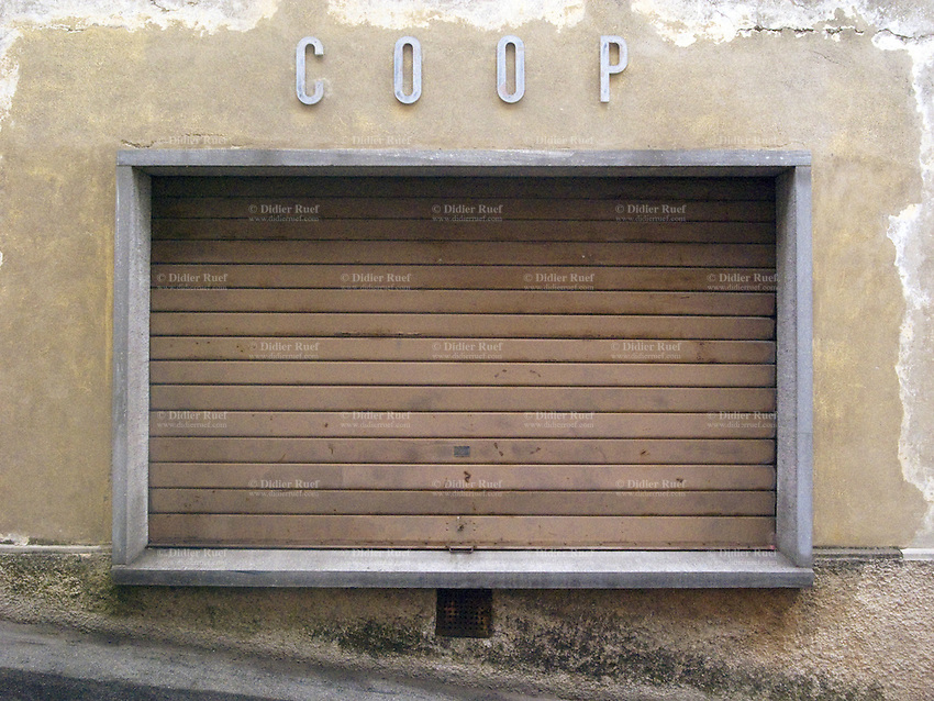 Switzerland. Canton Ticino. Vacallo. The closed shutters of the Coop store. Retail business on a sunday afternoon.  21.03.10 © 2010 Didier Ruef