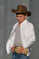 Boy, 8-11, wearing cowboy hat stands at a grain elevator on a farm