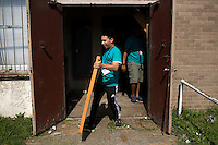 """Donald Franks moves old furniture to a dumpster during """"Circle the City with Service,"""" the Kiwanis Circle K International's 2015 Large Scale Service Project, on Wednesday, June 24, 2015, at the Friendship Westside Center for Excellence in Indianapolis. (Photo by James Brosher)"""