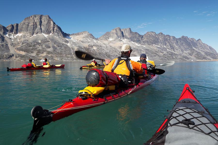 Sea kayakers paddling on Ikaasatsivaq Fjord, Ammassalik Island, East Greenland