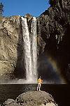 Snoqualmie Falls with fisherman on rock fishing with rainbow.