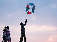 Local man with his family flying kite on the promenade in Galle, Sri Lanka