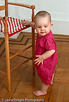 10 month old baby girl standing holding onto chair motor development vertical