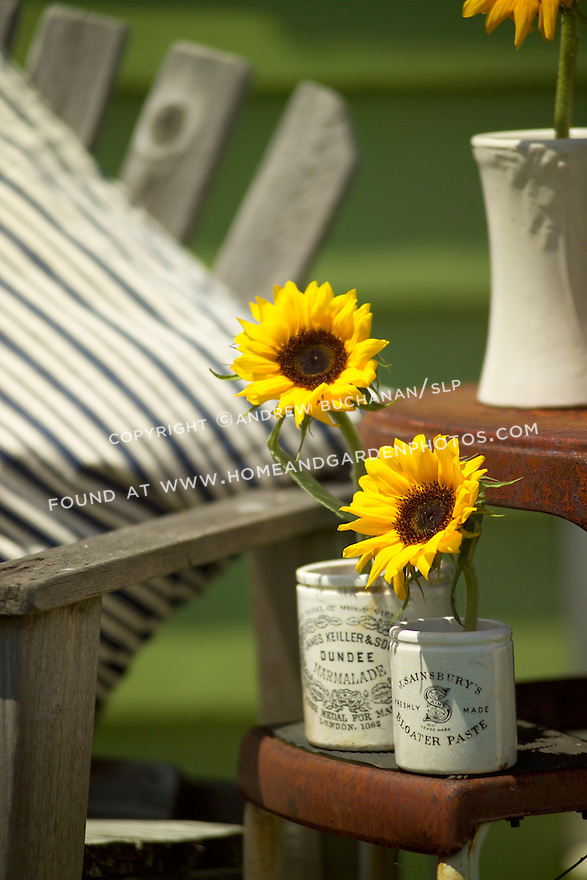 Antique and collectable stores offer all manner of everyday objects that can find new life as vases and stem holders for flowers.  Here, single stems of sunflowers rest in old British crocks set out on a well-used stepladder.  A wooden bench, striped ticking pillow, and a good book complete the backyard scene.