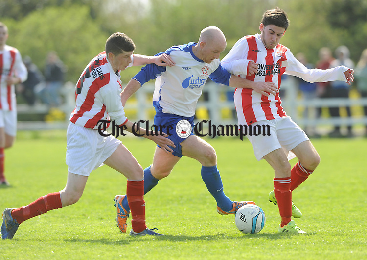 Alan Brigdale of Newmarket in action against Craig Madigan and Chris O Neill of Geraldines during their Munster Junior Cup Semi-final at the County Grounds. Photograph by John Kelly.