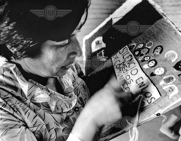 A female relative of a political prisoner sews an embroidered panel.