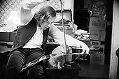 """PD-691226B. """"Paul deLay playing saw. very late, after Mixed Blood Saturday show at Charix. Bugs -- kitten. 1/8th at f 3.5. December 26, 1969"""""""