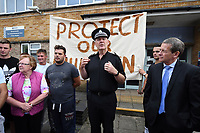 "Pictured: A Dyfed Powys Police officer address the protesters gather outside Pembroke police station, west Wales, UK. Thursday 13 July 2017<br /> Re: Angry protesters staged a six-hour demonstration through the night after concerns a convicted criminal was living in their community.<br /> Crowds of people chanting and setting fire to bins gathered in Gwilliam Court, in Monkton, Pembrokeshire, at 9.30pm on Tuesday.<br /> Police were called and took two people from a property before the disturbance ended six hours later.<br /> On Wednesday, about 100 protesters gathered outside a council office.<br /> The crowd outside the office in Argyle Street, Pembroke Dock, were shouting and chanting about the situation in Monkton, with some saying they were not leaving until they had answers.<br /> Dyfed-Powys Police said officers were present and ""engaging with the community about their concerns""."