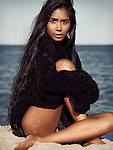 Beautiful young woman with long dark hair wearing a black turtleneck sweater sitting on sand at the beach Image © MaximImages, License at https://www.maximimages.com
