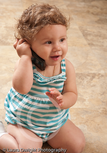13 month old baby girl at home holding cellular telephone holding it to ear as if talking on the phone pretend play talking on phone vertical