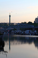 Paris Right Bank: A view of the port de l'Arsenal in Paris (it links the Canal de Saint Martin to place de la Bastille), with its boats, its typical bridge, and the column of July that reflects itself onto the flat water surface on the background, in the sunrise light.<br /> <br /> You can download this file for (E&PU) only, but you can find in the collection the same one available instead for (Adv).