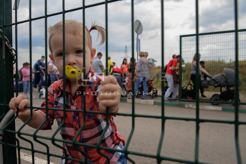 A child behind the gate of the border between Ukraine and Russia at Izvarine check point - one of border crossings controlled by Luhansk Peoples Republic. According to rebels around 5 thousand people leave Ukraine every day through Izvarine border crossing. June 26, 2014
