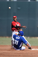 Cincinnati Reds shortstop Cory Thompson (15) turns a double play as Brandon Dulin (31) slides in during an Instructional League game against the Kansas City Royals on October 16, 2014 at Goodyear Training Complex in Goodyear, Arizona.  (Mike Janes/Four Seam Images)