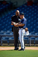 Mississippi Braves manager Chris Maloney (7) makes lineup changes with umpire Jose Navas during a Southern League game against the Jacksonville Jumbo Shrimp on May 5, 2019 at Trustmark Park in Pearl, Mississippi.  Mississippi defeated Jacksonville 1-0 in ten innings.  (Mike Janes/Four Seam Images)