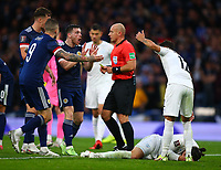 9th October 2021; Hampden Park, Glasgow, Scotland; FIFA World Cup football qualification, Scotland versus Israel;  Ofri Arad of Israel clutches his face as Scotland players speak to the referee