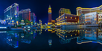 Nighttime panorama of the Vegas replica Venetian casino and the City of Dreams, with beautiful water reflections on the large pond in Macao, China