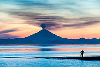 Man watches the plume of gas and vapor vent from the summit of Mt. Redbout volcano (10,191 ft), of the chigmit mountains, aleutian range. view across Cook Inlet approximately 50 miles, at sunset, southcentral, Alaska.