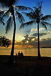 Enjoying the brilliant and warm colors of a hawaiian sunset from Magic Island on Oahu. A couple sit close to each other.