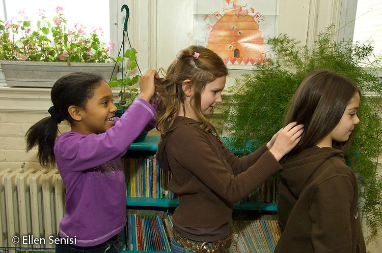 MR / Schenectady, New York. Elmer Avenue School (urban public school). 3rd grade classroom. Friends fix each others hair at free time. Left: girl, age 8, African-American / Puerto Rican-American; center: girl, age 8; right: girl, age 8. MR: Fra6, Mit10, Bro10. ID: AH-FRD. ©Ellen B. Senisi.