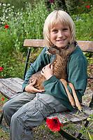 Rehkitz, Reh-Kitz, verwaistes, pflegebedürftiges Jungtier wird in menschlicher Obhut großgezogen, Kind, Junge sitzt auf einer Gartenbank und hat zahmes Kitz auf dem Arm, Tierkind, Tierbaby, Tierbabies, Europäisches Reh, Ricke, Weibchen, Capreolus capreolus, Roe Deer, Chevreuil