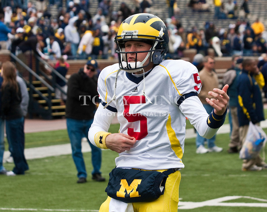 Michigan quarterback Tate Forcier (5) strums an imaginary air guitar to music played through the Michigan Stadium loudspeakers as the team warms up before the Wolverines' spring football game, Saturday, April 17, 2010, in Ann Arbor, Mich. (AP Photo/Tony Ding)