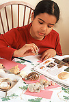 9 year old girl at home working on shell collection using photos and descrriptions in book to categorize shells vertical