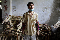 A worker in a factory that produces furniture made from bamboo. This one factory processes 800 bamboo trees (approximately 20 tons) per day, in southern Sichuan.